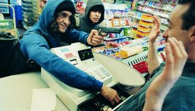 High Angle View of Two Robbers Robbing a Cash Till and Threatening a Shop Assistant with a Gun