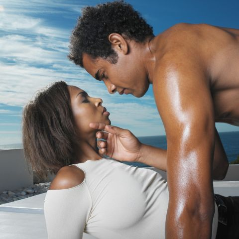 a young man leaning over a woman caressing her face