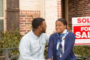 Excited couple in front of first home real estate purchase.