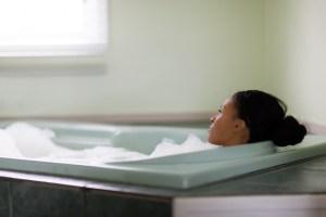 Young woman relaxing in bubble bath gazing through window