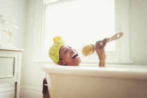 Playful mature woman singing into loofah brush in bathtub