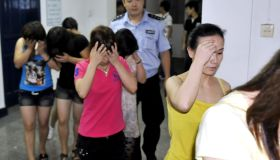 Chinese police lead away a group of youn