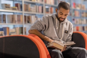 Handsome afro american university student studying alone in a campus library