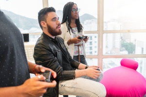 colleagues playing video game during break in creative office