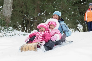 Mother and daughters sledding on snowy hill outdoors