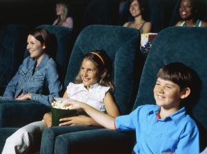 Children watching a movie in a movie theatre and eating popcorn