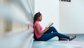 Young woman reading a book outside a campus building