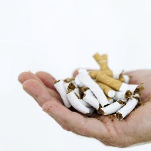 close-up of a man's hand with crushed cigarettes