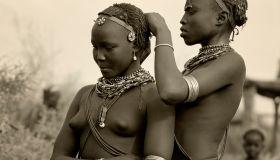 Ethiopia, Omo Delta. A Dassanech girl braids her sister's hair at her village in the Omo Delta