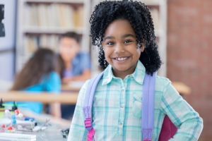Elementary age little girl smiles for camera at school