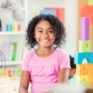 Little girl smiles for camera in after school care classroom