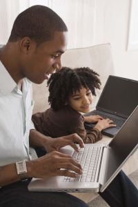 Father and daughter using laptop computers
