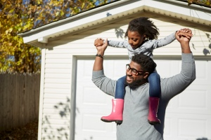 Mature man carrying daughter on shoulders by residential garage