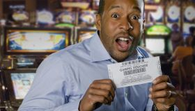 Excited African American man holding gaming voucher in casino