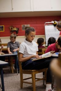 Girl reading book in classroom, children in background