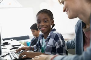 Portrait smiling pre-adolescent girl at computer in classroom