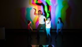 Scientist and children casting multicolor shadows on projection screen in science center theater