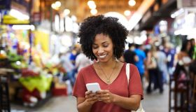 Smiling woman using smart phone at supermarket