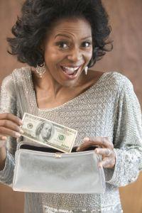 Woman putting 100 dollar bill into her purse